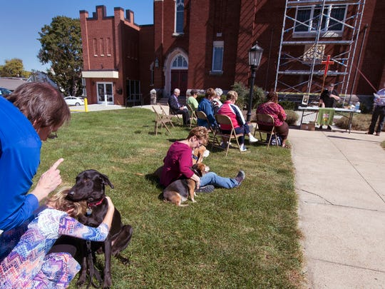 Marc Olson, left, tells an attentive Watson, a lab mix, to be good at the beginning of Blessing of the Animals 2017