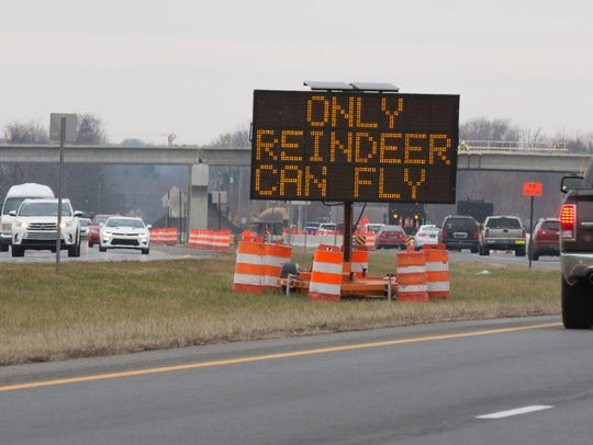 Drivers pass an electronic DelDOT sign, with a reference