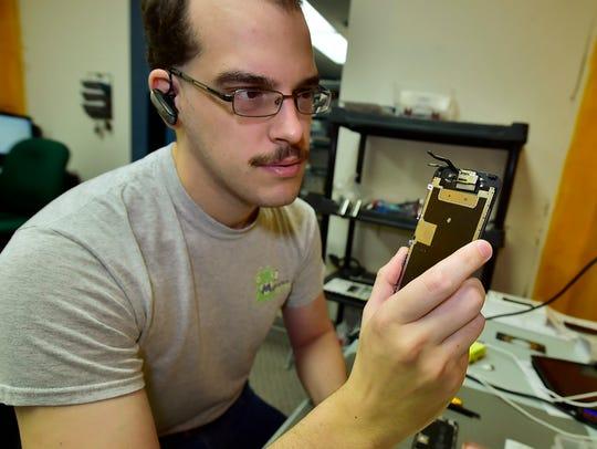 Service tech Matthew Wagner repairs cell phones Thursday,