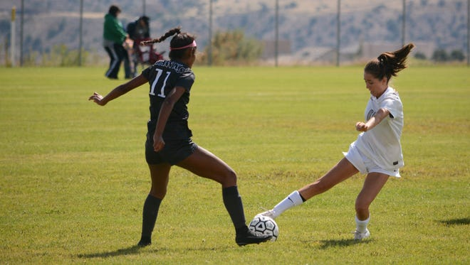 Piedra Vista's Whitney Chacon looks to pivot to the left moving the ball down the field against Volcano Vista's Dalis Bruce, left, during the first half of Saturday's District 1-6A match at PVHS.