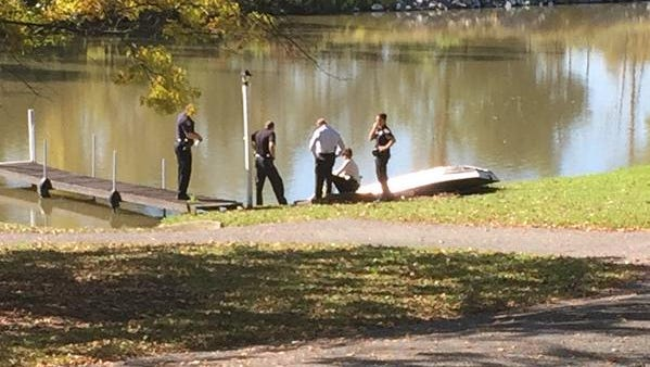 Police examining the body of Douglas J. Wilson, found on the edge  of the Erie Canal Thursday.