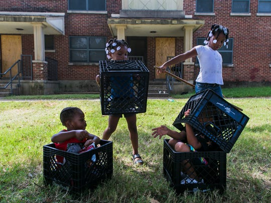 Terrion Nevels (left), 2, hands his neighbor Carlos Webb, 4, a potato chip as the two boys play with Nevels' sisters: Terriney Nevels (second from left), 3, and Mikerriya Murray, 6, at Foote Homes September 19, 2016.