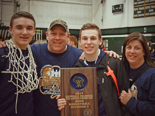 The Dieringer family from left: Evan, Derek, Ryan, Becky. Evan Dieringer has a net around his neck and Ryan holds the sectional plaque with their parents after the Marshfield Columbus Dons boys basketball team won a Division 5 sectional.