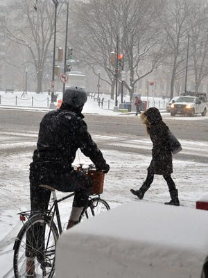 People trek through a snowstorm in the Washington, D.C., area, which snarled the morning rush hour on Jan. 6, 2015.