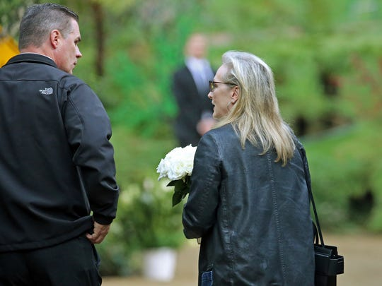 Meryl Streep arrives with flowers at a memorial service