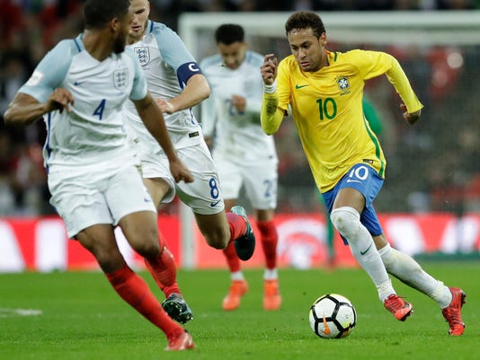 Brazil's Neymar takes the ball forward watched by England's Joe Gomez, left, and England's Eric Dier during the international friendly soccer match between England and Brazil at Wembley stadium in London, Britain, Tuesday, Nov. 14, 2017. (AP Photo/Matt Dunham)