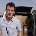 Peter Kassig stands in front of a truck filled with supplies for Syrian refugees.