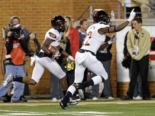 Louisville's Shaq Wiggins, left, returns an interception against Wake Forest as Chucky Williams, right, celebrates in the second half of an NCAA college football game in Winston-Salem, N.C., Friday, Oct. 30, 2015. Louisville won 20-19. (AP Photo/Chuck Burton)