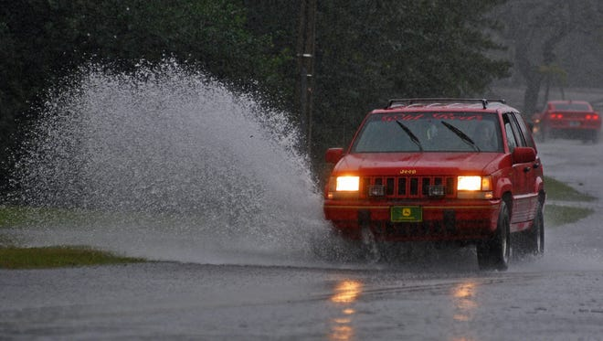A Jeep drives through standing water along Park Avenue in Titusville.