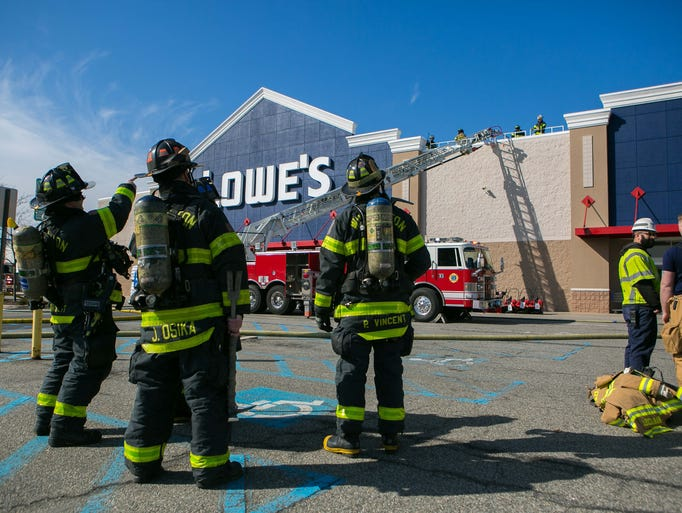 Firefighters continue to work on a fire at Lowe's located