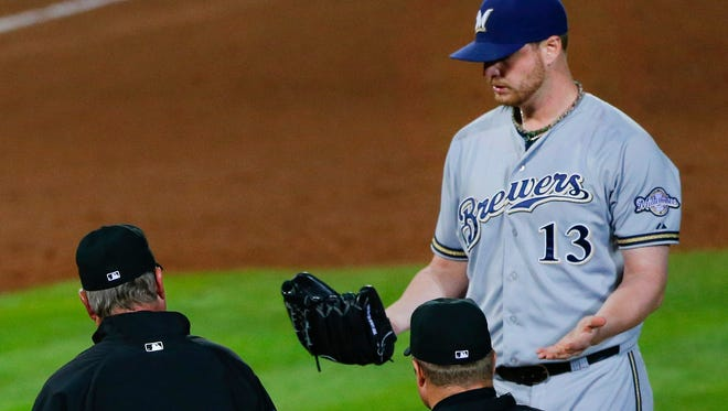 The umpiring crew walks to the mound to talk to Milwaukee Brewers relief pitcher Will Smith before ejecting him in the seventh inning against the Atlanta Braves on Thursday, May 21, 2015, in Atlanta.