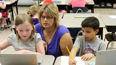 Teacher Wendi Gruber helps her students use laptops in a pilot test program as part of a state initiative to develop a Common Core curriculum.