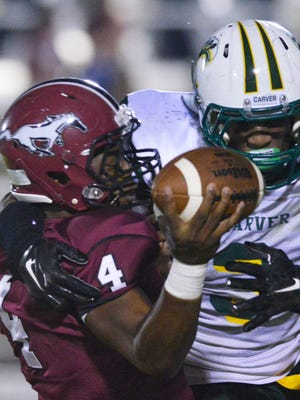 Stanhope Elmore's Bishop Frazier (4) is sacked by Carver's  Lyndell Wilson (3) during their game at Foshee Henderson Field in Millbrook, Ala., on Friday, Sept. 16, 2014