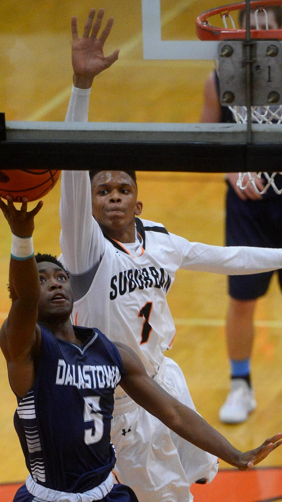 Dallastown's Donovan Catchings scores in the final moments of the first half through the defense of York Suburban's Chey Carter during the boys' basketball game on day one of the York Suburban Tip Off Tournament at York Suburban High School Friday, December 4, 2015. Dallastown beat York Suburban 61-59.