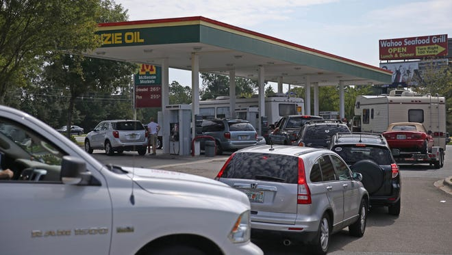 Lines of cars at the McKenzie gas station on North Monroe stretch into the street Friday.