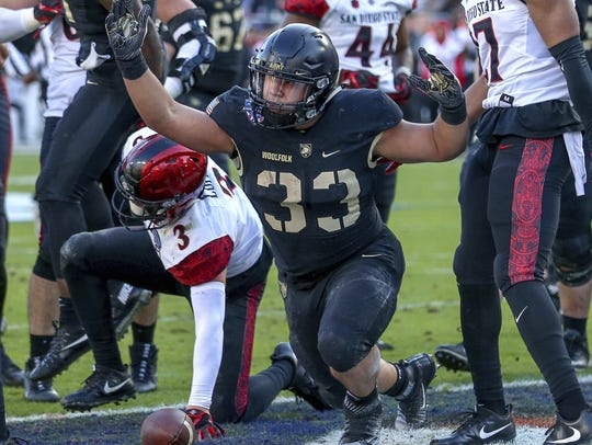 Army running back Darnell Woolfolk, center, reacts