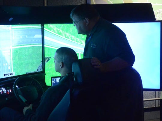 Brandon Hatch operates a driving simulator at Kellogg Community College while, Chet Dalski, KCC's Director of Emergency Medical Services, watches. The KCC simulator will be incorporated this fall in the emergency response driving course.  driving simulator