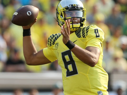 FILE - In this Sept. 6, 2014, file photo, Oregon's Marcus Mariota passes down field against Michigan State during the second quarter of an NCAA college football game in Eugene, Ore. Mariota goes into Saturday's Dec. 13, 2014, Heisman Trophy ceremony as the clear front runner.  (AP Photo/Chris Pietsch, File)