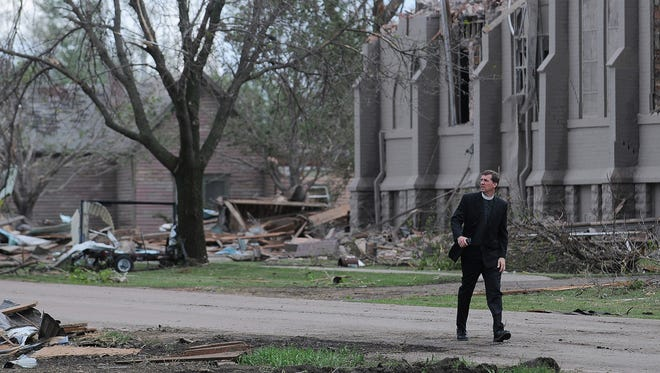 Rev. David Otten--from Immanuel Lutheran Church in Dimock, S.D., who was filling in for Rev. Brian Bucklew at Zion Lutheran Church, but wasn't in the church when the tornado hit--walks down Main Street in Delmont, S.D., in front of Zion Lutheran Church on Sunday, May 10, 2015, after a tornado tore through the area damaging homes and businesses on Sunday morning.