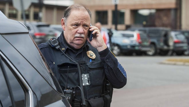 Hinesburg Police Chief Frank Koss answers a call after students were evacuated from Champlain Valley Union High School in Hinesburg on Tuesday, December 15, 2015, after a staff member found a written bomb threat at the school.  They were bused to the town post office before being sent home for the day.