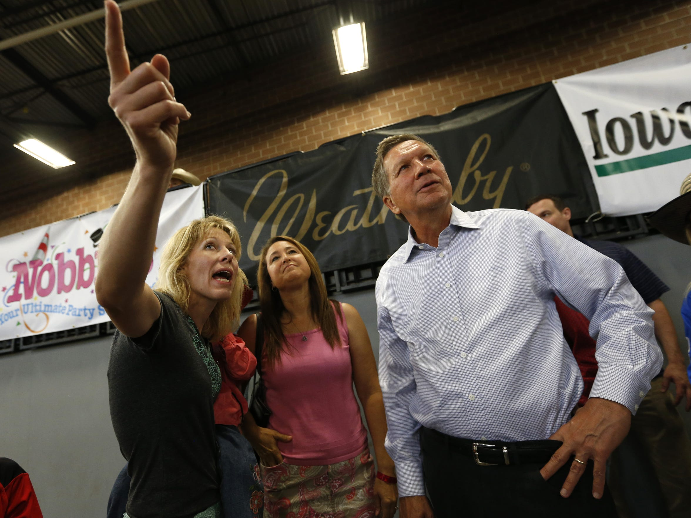 Tess Elshoff of New Knoxville, Ohio (from left) and Rita Jarvis of Salem, Ohio, explain how the breakaway event is scored to Ohio Governor John Kasich Wednesday, June 24, 2015, as Kasich stops by the National Junior High Finals Rodeo event at the Iowa State Fair Grounds in Des Moines, Iowa.