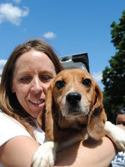Marcy Rydd, a former staff member with Pets Alive in Middletown, N.Y., holds a beagle in 2010 after its rescue from a shuttered testing lab formerly owned by Shri Thanedar.