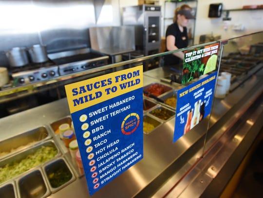 Kaley White makes a burrito behind a list of Hot Head's