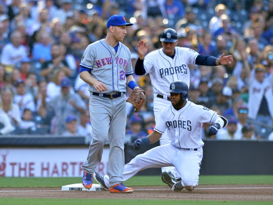 Apr 28, 2018; San Diego, CA, USA; San Diego Padres center fielder Manuel Margot (center) slides in safely with a two RBI triple in the first inning as New York Mets third baseman Todd Frazier (left) looks on at Petco Park.