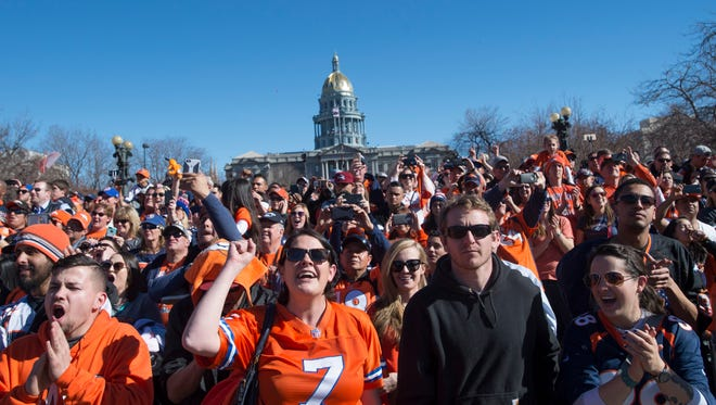 Fans cheer for the Denver Broncos as they take the stage in Civic Center Park during a Super Bowl championship celebration Tuesday, February 9, 2016.
