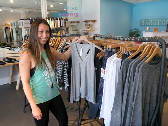 Alison Keating, owner of Barefoot, shows off merchandise in her Spring Lake store.