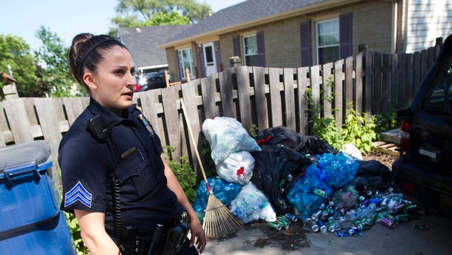 In this file photo, Sgt. Theresa Janick stands outside of a home littered with trash while taking part in the Community Prosecution Unit's Action Day on  on June 10, 2015.