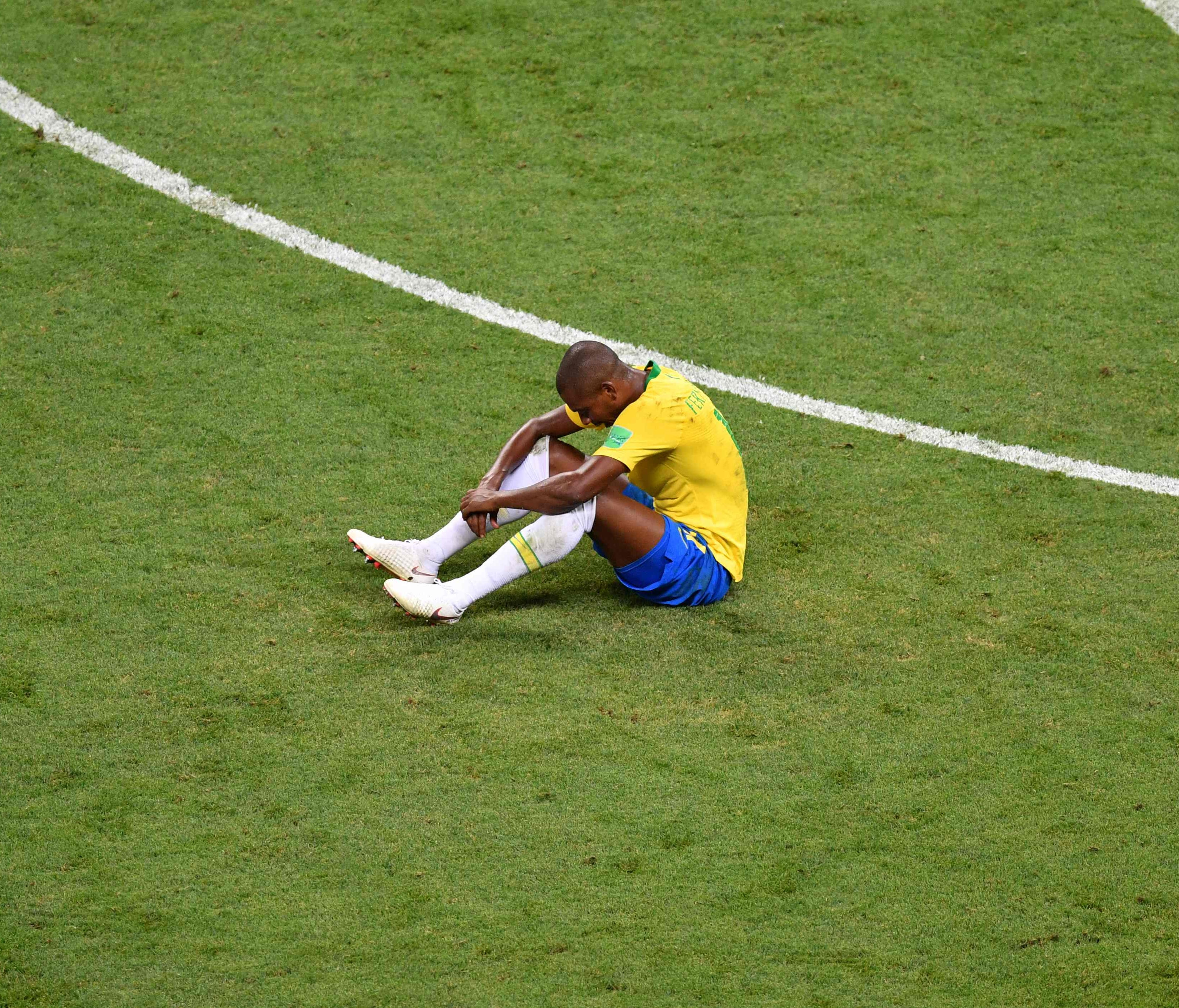 Brazil midfielder Fernandinho sits on the field after the loss to Belgium.