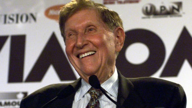 In this 1999 file photo, Viacom Chairman Sumner Redstone smiles during the announcement of a merger between CBS and Viacom in New York.