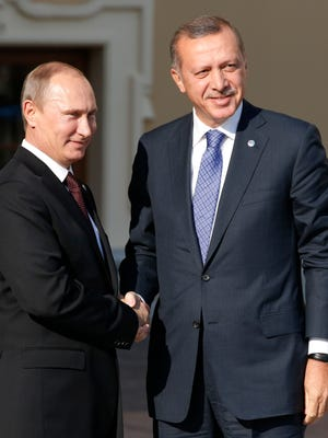 Turkey's Prime Minister Recep Tayyip Erdogan, right, shakes hands with Russian President Vladimir Putin during arrivals for the G-20 summit in September 2013.