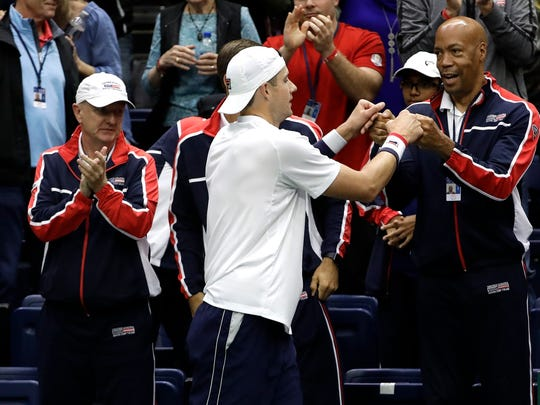 John Isner, of the United States, celebrates with his team after defeating Joris De Loore, of Belgium, in a Davis Cup quarterfinal singles tennis match Friday, April 6, 2018, in Nashville, Tenn. (AP Photo/Mark Humphrey)