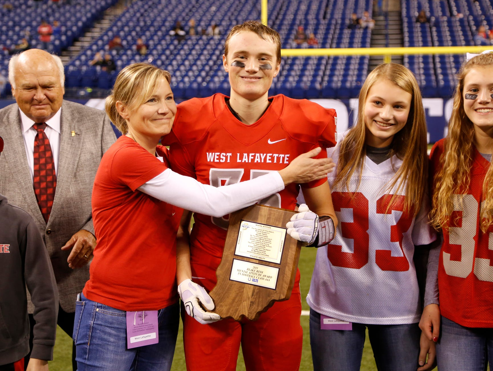 West Lafayette's Jack Folkers is embraced by his mother, Brooke Folkers, after he received the Mental Attitude Award following the Red Devils game against Bishop Chatard in the Class 3A state finals Friday, November 27, 2015, at Lucas Oil Stadium in Indianapolis. West Lafayette fell to Bishop Chatard 31-7.