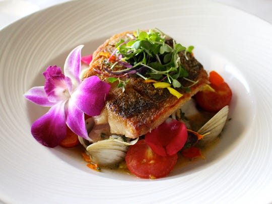 Gulf snapper is pan roasted and served over an herbed potato, cherry tomato, artichoke and clam stew at Mad Hatter Restaurant on Sanibel.