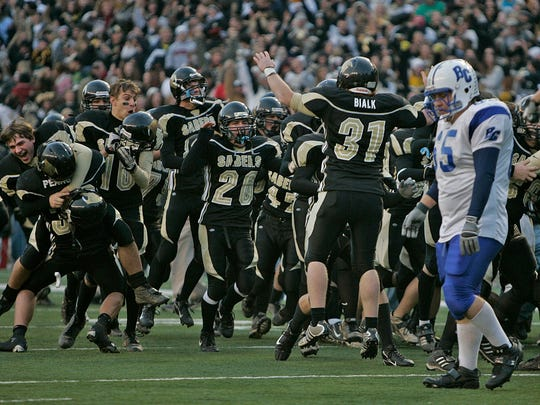 Brookfield Central's Jacob Glickstein walks off the field as the Franklin bench erupts following the Sabers' 36-29 overtime victory in the WIAA Division 2 state championship game Nov. 17, 2006, at Camp Randall Stadium.