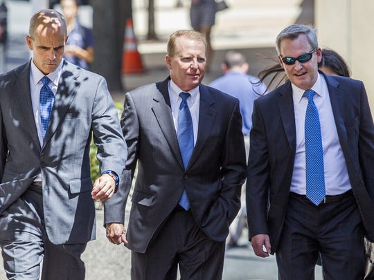 David Gibson (center) walks in the federal courthouse in Wilmington flanked by attorneys in 2015.