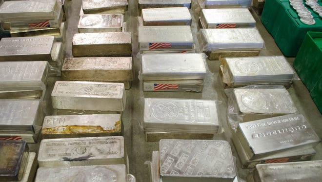 These bars of silver and dozens of firearms, as seen Nov. 20, 2015, were among the items seized during an early November 2015 raid at a property south of Wheeling, Indiana.