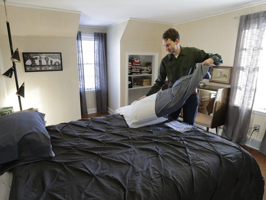 Airbnb host Joshua Skog changes linens in a room at