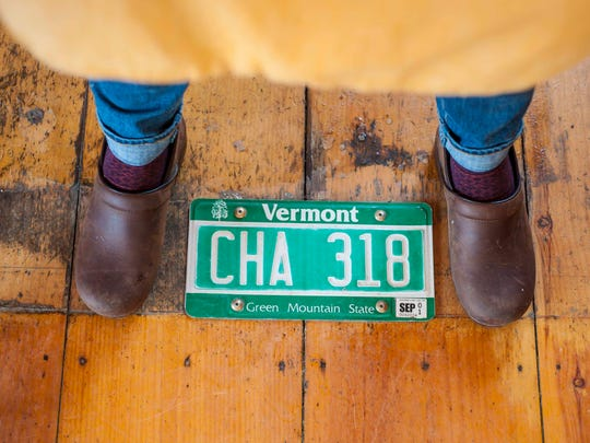 Amy Gifford of the Richmond Community Kitchen stands astride a license plate that first served as a quick patch for the floor and then became permanent.  Seen on Wednesday, February 28, 2018.