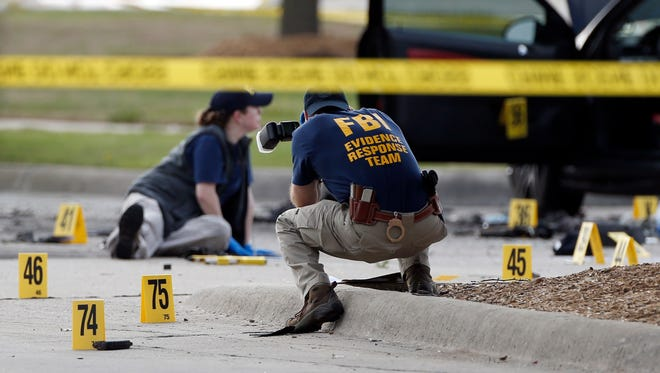 FBI crime scene investigators document the area around two deceased gunmen and their vehicle outside the Curtis Culwell Center in Garland, Texas, Monday, May 4, 2015. Police shot and killed the men after they opened fire on a security officer outside the suburban Dallas venue, which was hosting provocative contest for Prophet Muhammad cartoons Sunday night, authorities said.