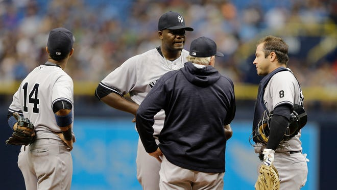 New York Yankees starting pitcher Michael Pineda, background center, talks to pitching coach Larry Rothschild, Starlin Castro and Austin Romine as he struggles during the first inning of a baseball game Saturday, May 28, 2016, in St. Petersburg, Fla.