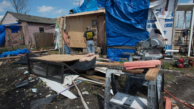 A month after a tornado ripped through town of Century, Chris Pace, left, gives homeowner Bobby Swords, right, a hand with repairs to his storm damaged property on Front Street.