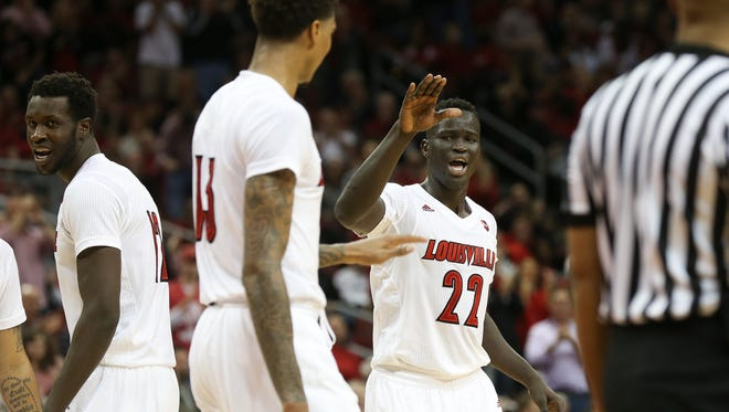 U of L's Deng Adel (22) celebrated a score while being fouled with teammate Ray Spalding (13) against Pitt during their game at the KFC Yum! Center.