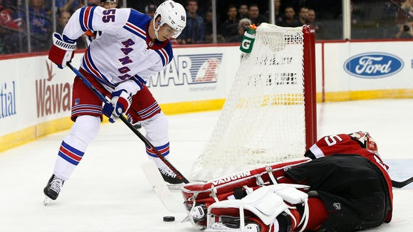 New York Rangers defenseman Nick Holden (55) attempts to get a rebound off a save by New Jersey Devils goalie Cory Schneider (35) during the first period of a preseason NHL hockey game in Newark, N.J., Saturday, Sept. 23, 2017. (AP Photo/Rich Schultz)
