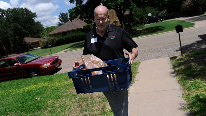 Ralph Goode carries a basket of items to a home in east Abilene Friday July 7, 2017. Goode works at United Supermarket's Market Street store in Abilene and delivers groceries to customers in the area as part of the store's Streetside service.