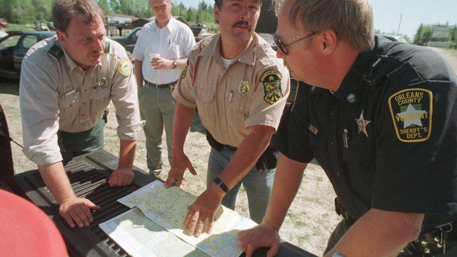 Law enforcement officers look over maps in Newport Center May 18, 1999, as they continue to search for two escaped convicts from the Northern State Correctional Facility who escaped on Sunday.