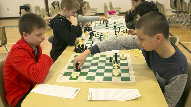 "Kevin Matthews, 12, watches as his opponent Jack Demetris, 11, makes a move. The Knights of Columbus held their annual ""Chess 'Round-Robin' Tournament Anyone?"" at Holy Family Roman Catholic Church on Saturday in Florham Park."